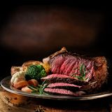 Rare Roast Beef. Meal with organic root vegetables and traditional Yorkshire pudding and roast potatoes. Shot against a dark rustic background with generous stock photos