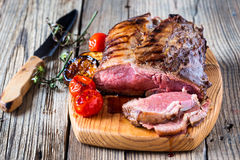 Rare roast beef. Rare roast sirloin of beef with roasted vegetables on rustic wooden background Royalty Free Stock Photo