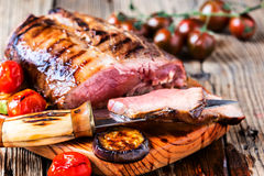Rare roast beef. Rare roast sirloin of beef with roasted vegetables on rustic wooden background Royalty Free Stock Photography