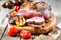 Rare roast beef. Rare roast sirloin of beef with roasted vegetables on rustic wooden background Royalty Free Stock Photos