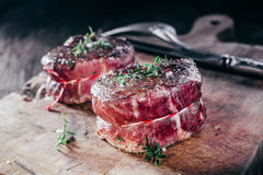 Rare Seasoned Venison Steak Filets on Wooden Board Stock Photo