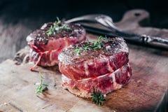 Rare Seasoned Venison Steak Filets on Wooden Board Stock Photo