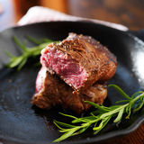 Rare steak cut in half on iron skillet with rosemary Stock Image