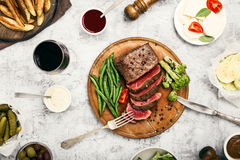 Rare steak with French beans and wine. Rare steak with side dish of French beans and glass of red wine on a wooden board, top view Royalty Free Stock Photo