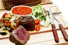 Rare steak with grilled vegetables on wooden plate Royalty Free Stock Photos