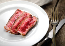 Rare steak medium roast with spices on a plate, knife and fork on a wooden background Royalty Free Stock Photos