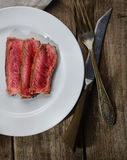 Rare steak medium roast with spices on a plate, knife and fork on a wooden background Stock Photography
