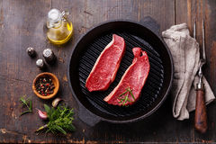 Rare Striploin steak in grill pan Stock Photos