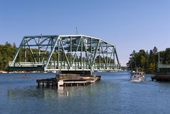 Swing Drawbridge Opens for Fishing Boat in Maine. Rare swing drawbridge provides opening for lobster boat to pass by in Boothbay region in maine Stock Image