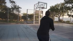Rare view of a long distance throw by young female basketball player practicing on the outdoors local baskeball court. Trees and sun shines on the background stock video footage