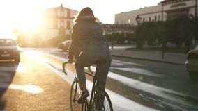 Rare view of a pretty caucasian female riding a bicycle in the morning empty street of a beautiful empty city. Young