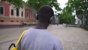 Rare view of young african american tourist listening to music using headphones and smart phone walk in beautiful, old