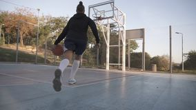 Rare view of a young girl basketball player training and exercising outdoors on the local court. Dribbling with the ball. Bouncing and make a shot. Low angle stock video