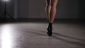 Rare view young sexy woman dressed in mesh tights and black leather underpants .Young girl in black high heels walks by. The empty room or fotoshooting studio stock video