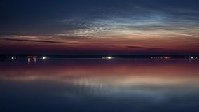 Noctilucent clouds over the lake. Rare weather phenomenon - high-altitude noctilucent clouds timelapse stock video