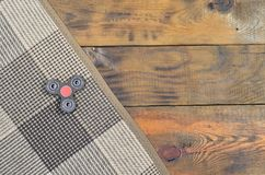 A rare wooden handmade spinner lies on a checkered plaid on a brown wooden background surface. Trendy stress relieving to royalty free stock photos