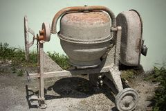 Rarely used Cement mixer standing near a wall. Cement mixers, or concrete mixers, allow users to mix large amount of cement, sand,. Rarely used Cement mixer stock photography
