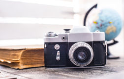 Rarity camera zenit with globe on the background. Rarity camera with globe and old book on the background Royalty Free Stock Image