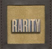 Rarity word framed. Rarity word assembled from vintage wooden letterpress inside stitched leather frame Stock Photography
