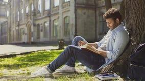 Rasa faceta obsiadanie pod drzewem w parku, czytelnicza książka, wolny czas, hobby Zdjęcia Royalty Free