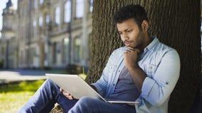Rasa młodego człowieka obsiadanie pod drzewem, patrzeje laptop, znacząco list Zdjęcie Royalty Free