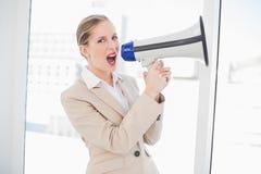 Rasande blond affärskvinna som ropar i megafon royaltyfri bild