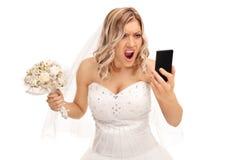 Rasande brud som ser hennes mobiltelefon Arkivbild