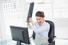 Rasande flott brun haired affärskvinna som kastar hennes tangentbord på hennes dator royaltyfri bild