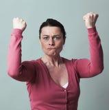 Rasande 40-talkvinna som böjer upp henne muskler för kvinnlig självständighet Royaltyfri Bild