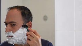 Rasatura dell'uomo con la lama della schiuma sullo specchio in bagno archivi video