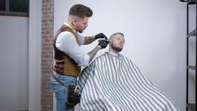 Rasatura della barba Capelli del fronte del ` s degli uomini di taglio del barbiere con il regolatore della barba al parrucchiere stock footage