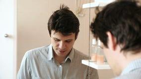 Rasature dell'uomo mentre guardando nello specchio Castana in una camicia della luce del plaid video d archivio