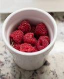 Rasberries in een Kop Stock Fotografie