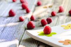 Rasberries on modern white plate on wood. Rasberries on modern white plate isolated on wood background Royalty Free Stock Photos