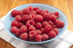 Rasberries. Pile of raspberries in a blue bowl on a table royalty free stock photo
