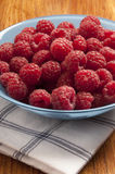 Rasberries. Pile of raspberries in a blue bowl on a table Royalty Free Stock Photos