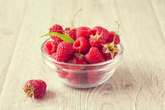 Rasberry in bowl. Rasberry in glass bowl on wooden background. Natural food Stock Photography