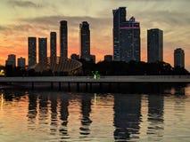 Rascacielos cerca del agua contra el sol poniente imagen de archivo