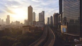 Rascacielos con el paso superior de la carretera en el tiempo de la salida del sol Imágenes de archivo libres de regalías
