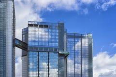 Rascacielos de cristal modernos del edificio con la reflexión azul del cielo nublado Fondo del distrito financiero Fotos de archivo libres de regalías