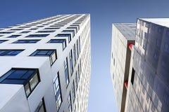 Rascacielos de dos vidrios en el cielo azul Imagen de archivo libre de regalías