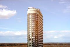Rascacielos moderno de la vista lateral en los rayos del sol y de nubes fotografía de archivo
