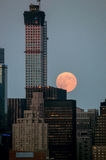 Rascacielos y luna grande Imagen de archivo