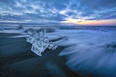Rasende Wellen, die Eisblöcke bei Sonnenaufgang auf Diamond Beach zertrümmern stockfotos