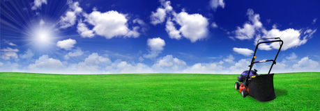 Rasenmäher auf grünem Feld Stockfoto