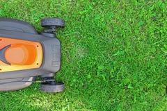 Rasenmähmaschine auf grünem Gras Stockbilder