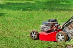 Rasenmäher auf grünem Gras Stockfotografie