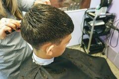 raseur-coiffeur Le plan rapproché des coupes de cheveux adolescent, maître fait la coupe de cheveux de cheveux dans le salon de c photographie stock