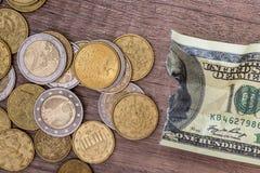 Rasgado 100 dólares con la moneda Imágenes de archivo libres de regalías