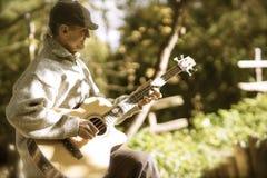 Rasguear la guitarra en luz de la tarde Imagenes de archivo
